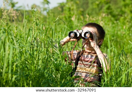 Young boy in a field looking through binoculars - stock photo