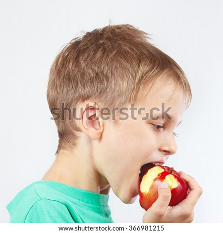 Young boy in a green shirt eating a red apple - stock photo
