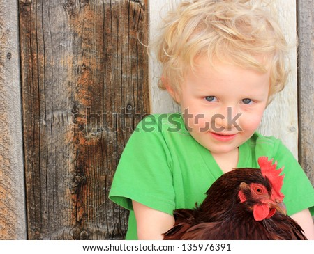 Young boy in a green shirt holding a chicken.