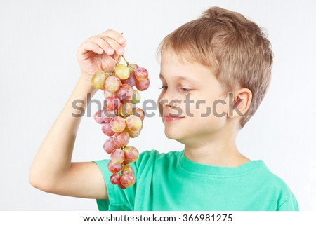 Young boy in a green shirt with a grape - stock photo