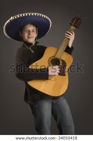 Young boy in a Mexican hat and with guitar on a black background.