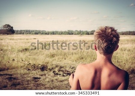 Young boy in a rural field looking into the distance. concept for future, discovery, exploring and education - stock photo
