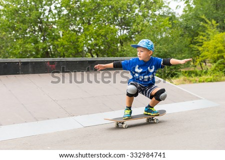 Young boy in a trendy blue outfit and safety gear practicing his skateboarding balancing on his board with outstretched arms - stock photo