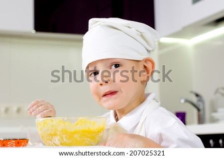 Young boy in a white toque learning how to cook standing at the kitchen counter with his mixing bowl full of ingredients with flour on his hands - stock photo