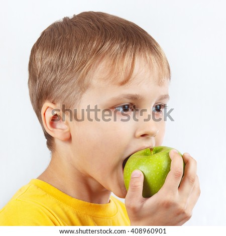 Young boy in a yellow shirt eating a green apple - stock photo