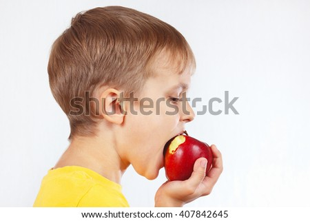 Young boy in a yellow shirt eating a juicy red apple - stock photo