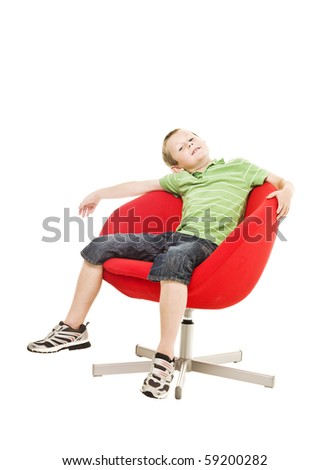 Young boy in an armchair isolated on white background - stock photo