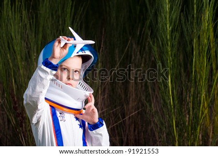 Young boy in an astronaut suit playing with a toy airplane. - stock photo