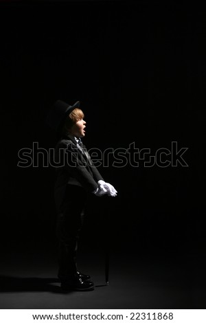 young boy in black tuxedo, top hat, and white gloves