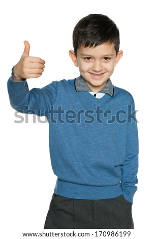 Young boy in blue pullover holds his thumb up on the white background