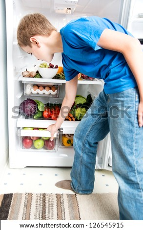 Young Boy in Blue Shirt  Reaching for Healthy Snack in Refrigerator Full of Fresh Foods O - stock photo