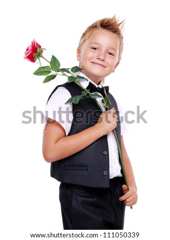 Young boy in bow tie and suit holding rose on his shoulder - stock photo