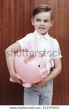 Young boy in braces holing large piggy bank  - stock photo