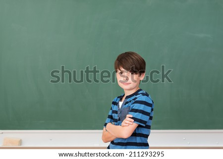 Young boy in class standing in front of a blank blackboard with copyspace with his arms folded looking at the camera with a smile - stock photo