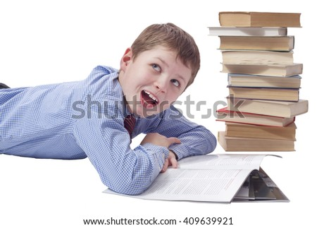 Young boy in classic  dress lying with heap of books on white ba - stock photo