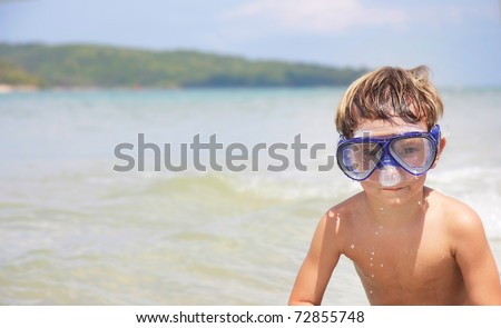 young boy in diving mask on sea background - stock photo