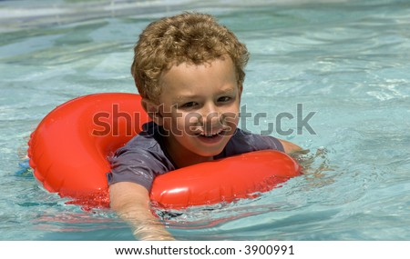 Young boy in float ring in swimming pool - stock photo