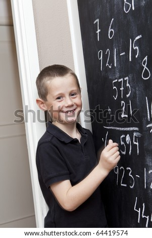 Young Boy in front of the blackboard at school - stock photo