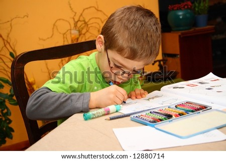 Young boy in glasses painting - stock photo
