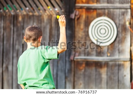 Young boy in green t-shirt playing darts outdoor