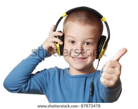 Young boy in headphones giving thumbs up sign - stock photo