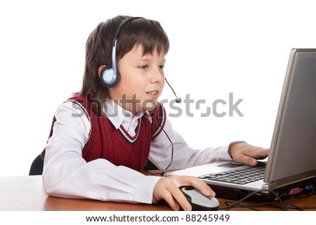 young boy in headset playing with laptop - stock photo