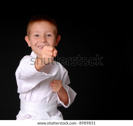 Young boy in karate outfit making fighting movement - stock photo