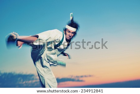 Young boy in karate uniform training at sunset  - stock photo