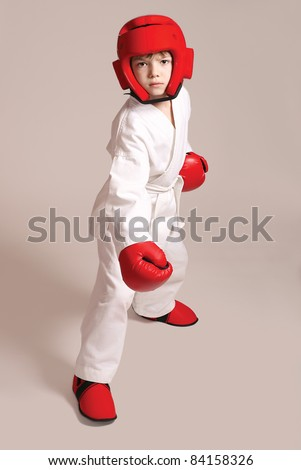 Young boy in kimono ready to fight on grey background - stock photo