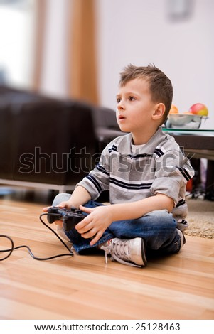 Young boy in living room with video game controller . - stock photo