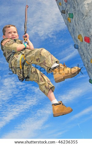 Young boy in military clothes practicing rappelling - stock photo