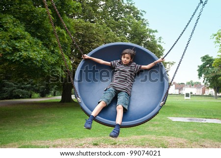 Young boy in playground swing