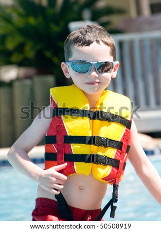 Young boy in pool wearing safety flotation - stock photo