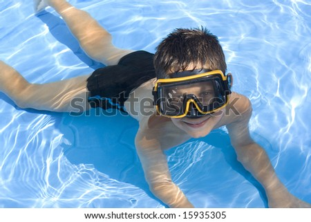 Young boy in pool with goggles on - stock photo