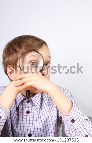 Young boy in purple shirt looking through a magnifying glass grimacing - stock photo