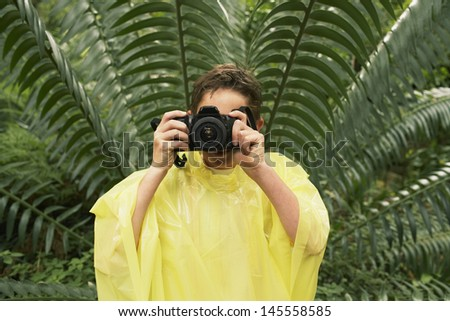 Young boy in raincoat taking photos in forest during field trip - stock photo