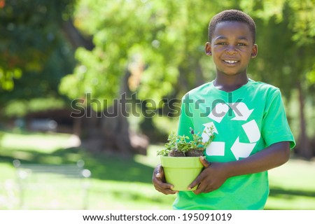 Young boy in recycling tshirt holding potted plant on a sunny day - stock photo