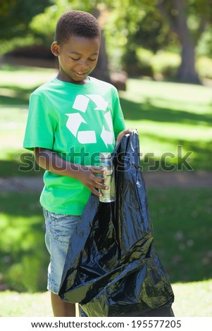 Young boy in recycling tshirt picking up trash on a sunny day - stock photo