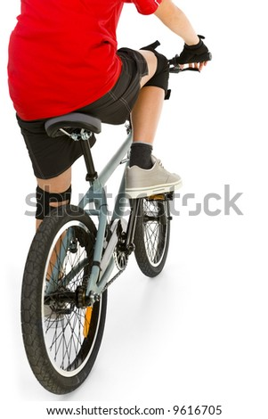 Young boy in red T-shirt cycling on BMX . Rear view. White background.