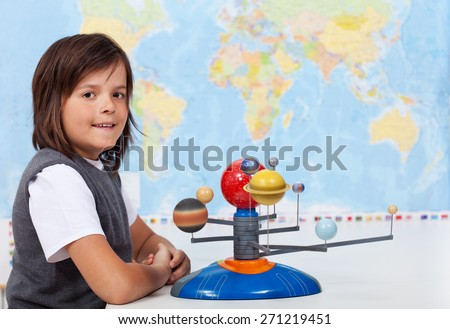 Young boy in school learning about the solar system - stock photo