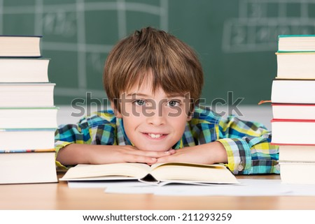 Young boy in school surrounded by two stacks of hardcover textbooks resting his chin on his arms smiling at the camera
