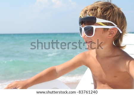 young boy in sun glasses on sea background - stock photo