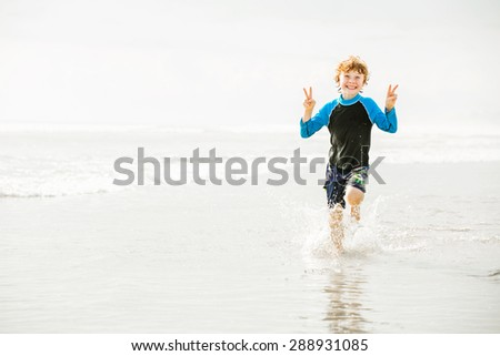 Young boy in swimming shorts and rash vest runs along Bali beach near sunset with reflection in the water