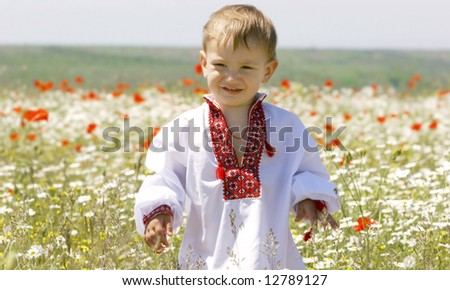 young boy in traditional clothes in flowers - stock photo