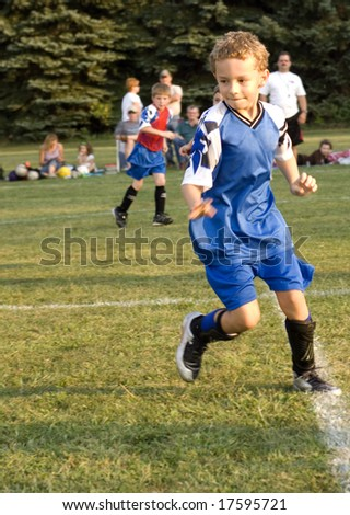 Young boy in uniform playing soccer - stock photo