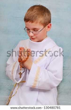 young boy in white alb going to the first holy communion and praying with wooden rosary - stock photo