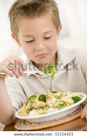 Young boy indoors eating pasta with brocoli - stock photo
