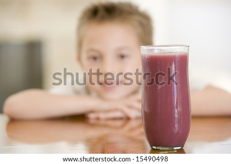 Young boy indoors with focus on juice glass - stock photo