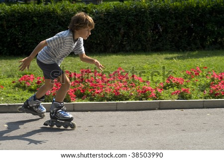 Young boy inline skating in park. - stock photo