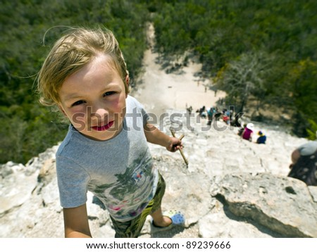 young boy is at the top of the pyramid Nohoch pyramid at Coba - stock photo